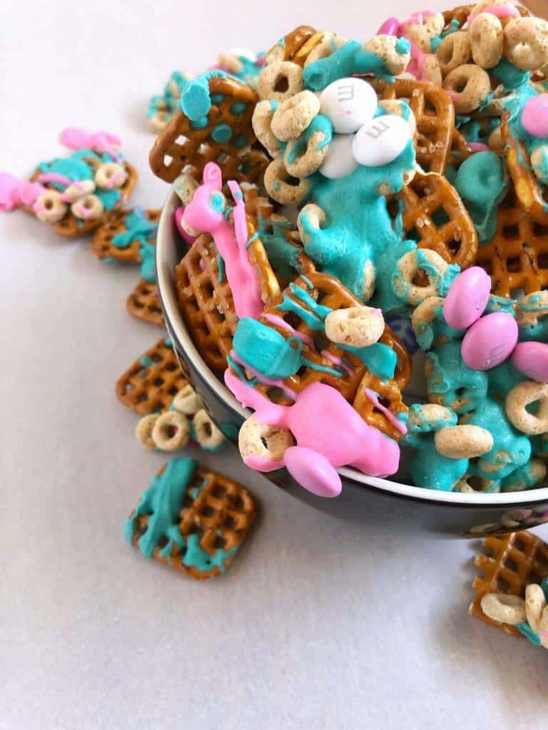 Trolls Birthday Party Snack Mix- A close up of a pink and turquoise chocolate snack mix drizzled over pretzels, cereal and topped with chocolate candies, an easy recipe for your next party.