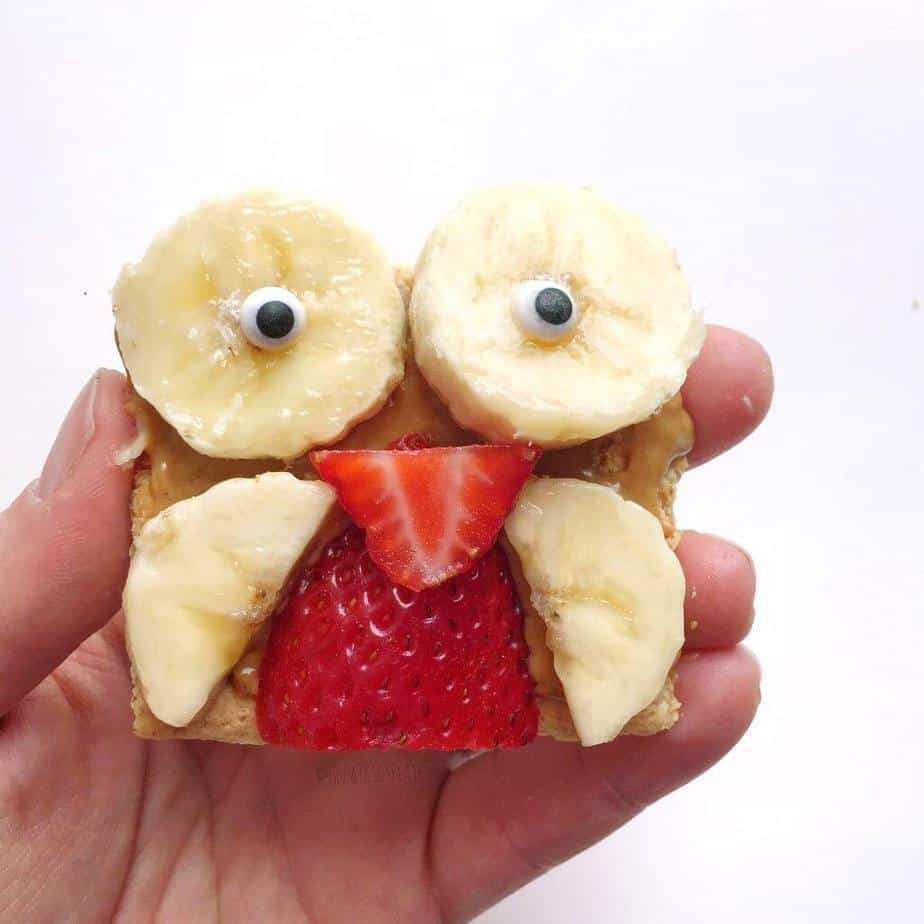 A close up of an owl shaped kids snack made of grahma cracker, peanutbutter, banana slices and strawberries held in a hand.