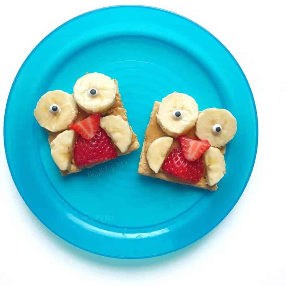 Two graham crackers covered in peanutbutter, banana slices and strawberry slices made into the shape of an owl on a blue plate, perfect for a kdis snack.