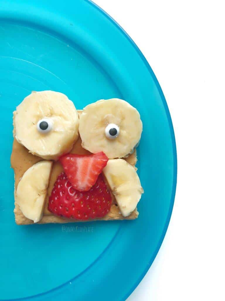 Close up of a graham cracker with peanut butter shaped like an owl. Banana slices make the owl's wings and eyes, and strawberry slices covers his belly and makes his beak.