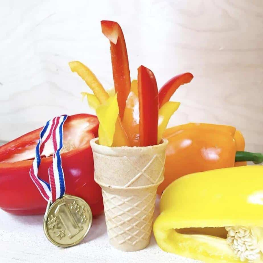 Red, yellow and orange bell peppers sliced into strips inside a plain ice cream cone in the shape of an olympic torch. snack for kids. Scattered around are more peppers and an olympic gold medal.