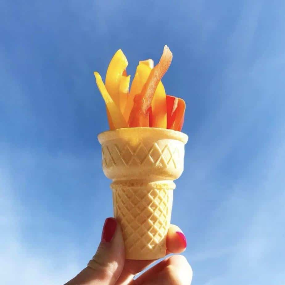 An olympic torch snack for kids made from an ice cream cone full of yellow, orange and red bell peppers. The snack is held up in front of a blue sky victorious, ready for the winter olympics.