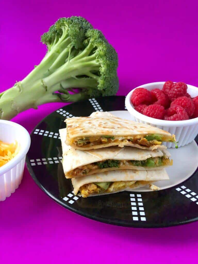 A stack of quesadillas filled with broccoli, egg, cheddar cheese sits in a stack on a plate. Sitting on the bright purple background is a broccoli, side of fresh raspberries and small side of cheese ready for a kid to have breakfast.