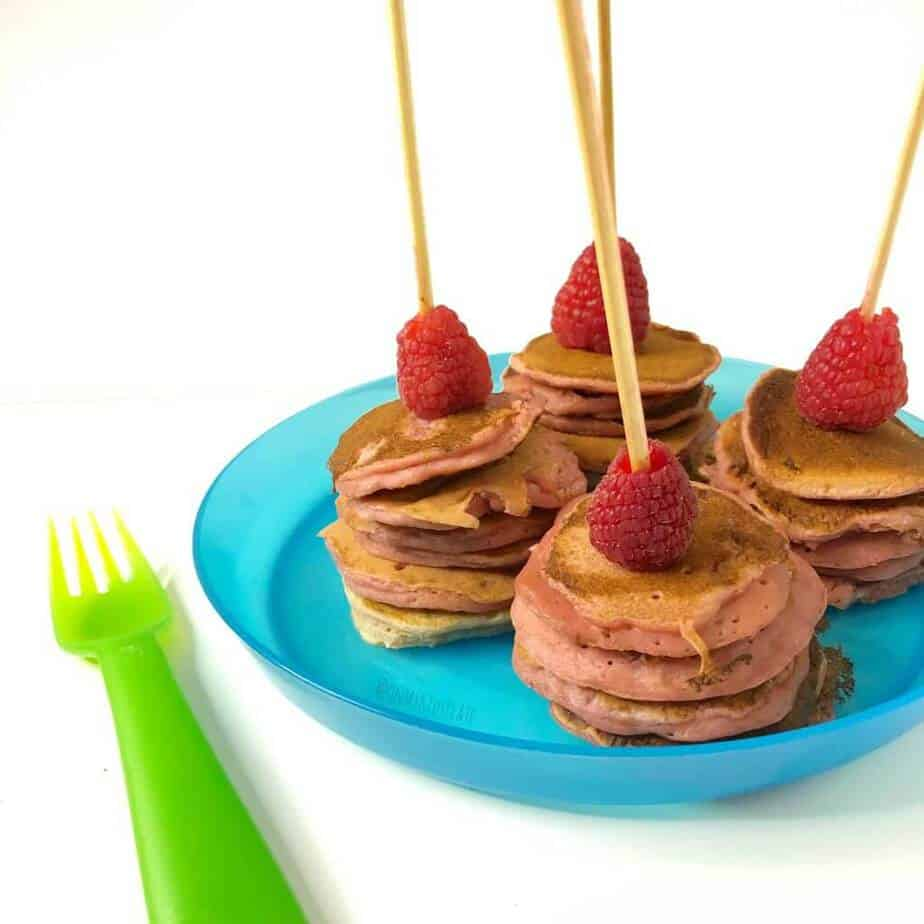 Four mini pink pancake kabob stacks on a blue kid's plate, each topped with a raspberry. A green kid's fork sits next to the plate.