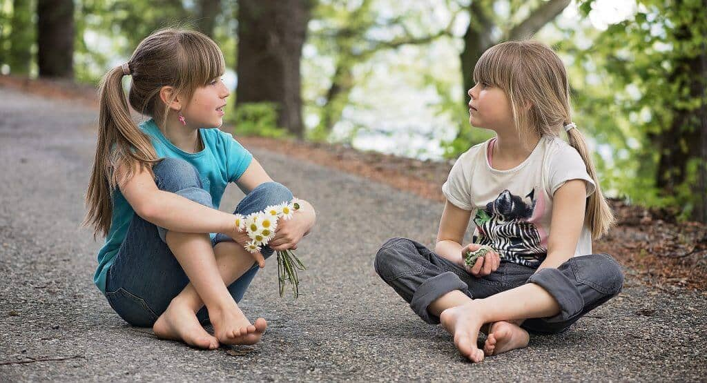 Two school age girls sitting outside, talking together.