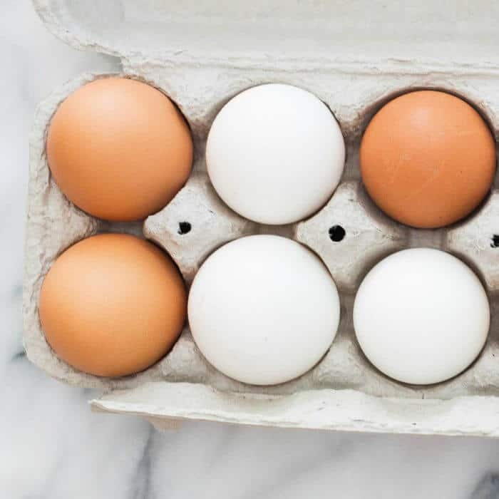 Three white eggs and three brown eggs sitting in an egg carton on a table top.