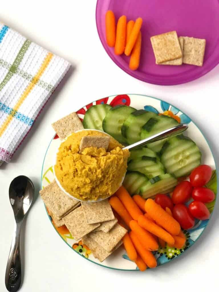 A small round platter of cucumbers, carrots, cherry tomatos and crackers sits wiht a small bowl of carrot hummus dip. In the dip is a cracker and a small kid's knife. Next to the plate is a small kid's spoon, a qhite dish towel with brightly colored stripes, and a purple kid's plate with a few carrots and crackers portioned on top.