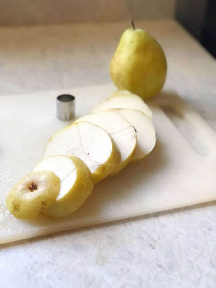 A paar sits on a kitchen counter on top of a cutting board sliced into rounds and scattered in a row. Behind on the cutting board sits a second whole pear and a small round cookie cutter.