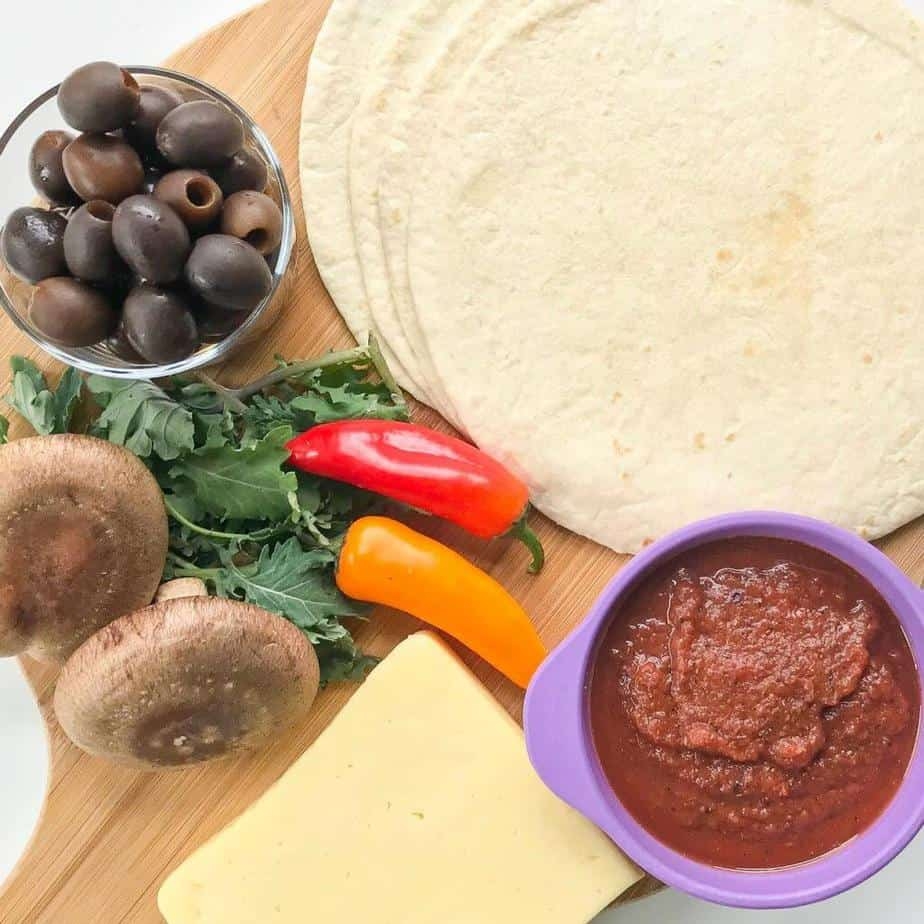 A wooden pizza paddle sits on a white table covered with ingredients including tortillas, pizza sauce, peppers, kale, mushrooms, a block of mozerella cheese and a small bowl of olives.
