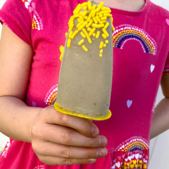 A little girl's hand holds a banana popsicle.