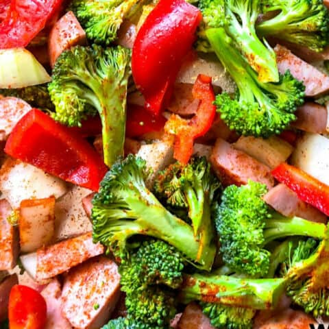 Smoked sausage mixed with roasted broccoli, peppers and onions close up on a pan.