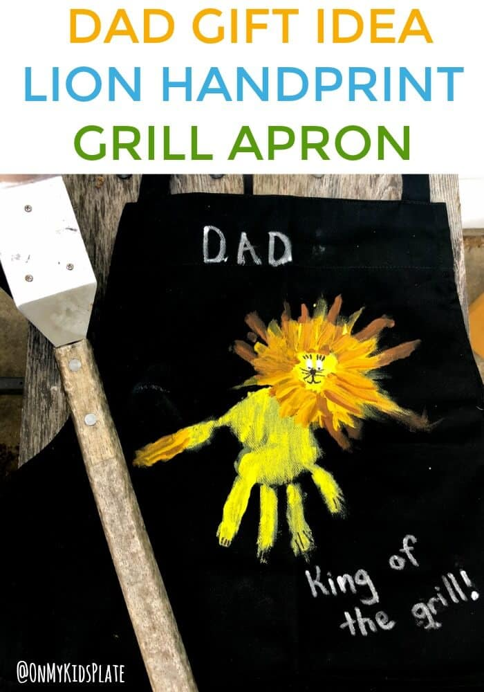 "A grill apron is laid next to a grill with a grill brush. We see a child's handprint on the front painted to look like a lion as a gift for Dad. The grill apron reads ""Dad, king of the grill"""