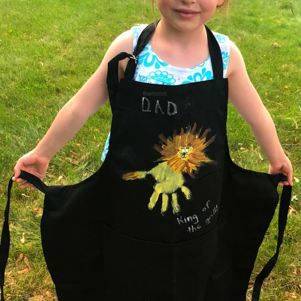 "A girl smiles wearing a DIY grill apron with her handprint print pained on the front to look like a lion. The apron reads ""Dad, king of the grill."""