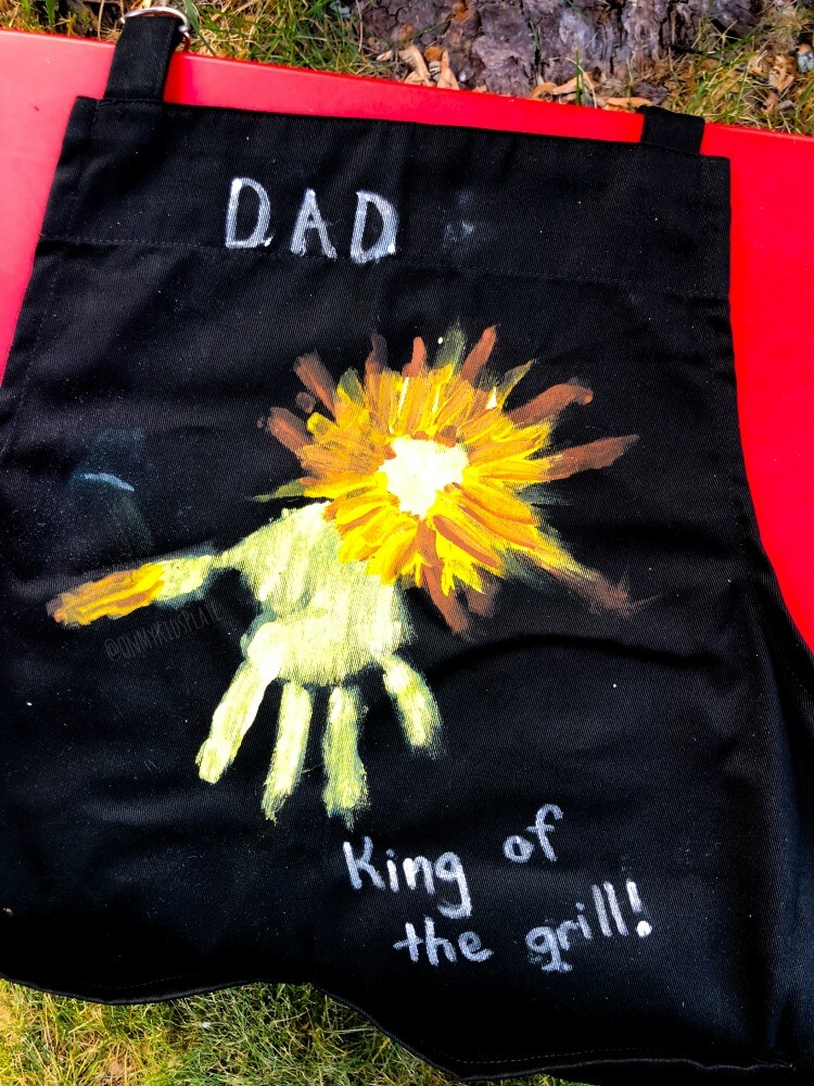 On a small table is a grill apron, almost finished painting with a handprint lion as a cute gift from a child for Father's Day.