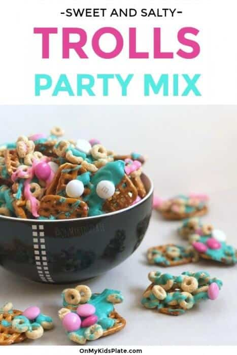 A bowl full of tasty sweet and salty sanck mix sits surrounded by colorful chocolates, Cheerios and pretzels ready for a kid's birthday party.