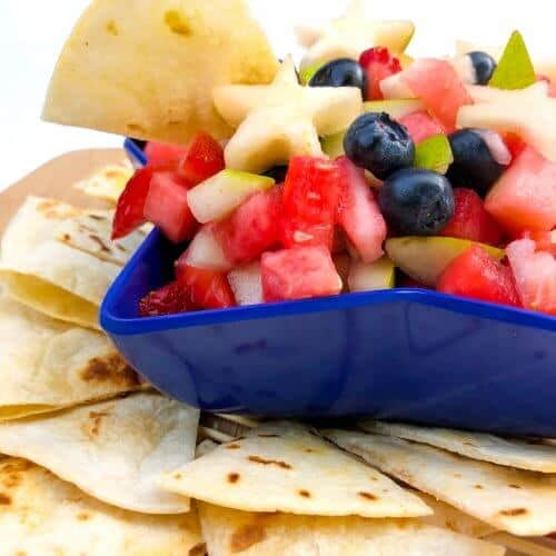 Side view of fruit salsa in a star-shaped bowl with a chip dipping into it, more chips scattered around the bowl