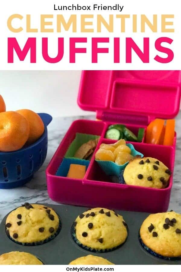 Clementine and chocolate chip muffins sit freshly baked in a muffin tin in front of a lunchbox packed with muffins, fruit, vegetables, cheese and sweet clementines.