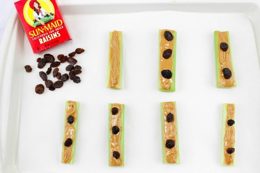 Seven slices of peanut butter sit on a tray garnished with raisins. A box of raisins sits on the tray with a few raisins scattered and ready to finish making the ants on a log.