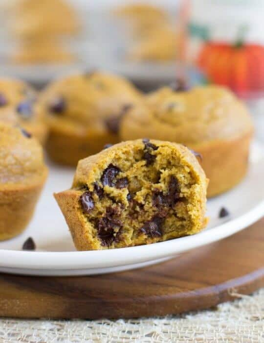 pumpkin chocolate chip muffin on a plate with a bite taken
