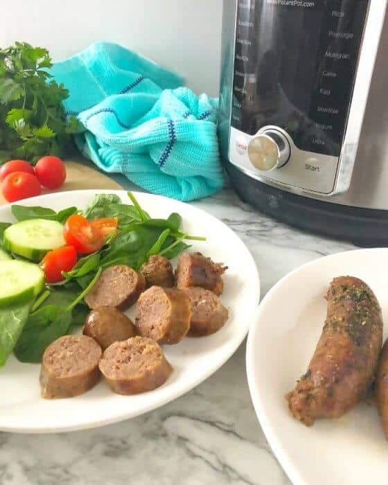 Sliced italian sausage on a plate next to a salad, with a serving plate of sausage next to it. In the background is in an instant pot, a kitchen towel, and tomatos and parsley on a cutting board.