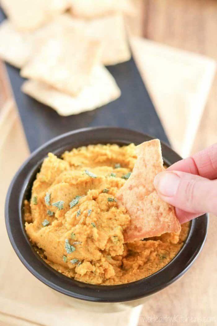 Orange hummus dip with a hand grabbing a scoop on a chip