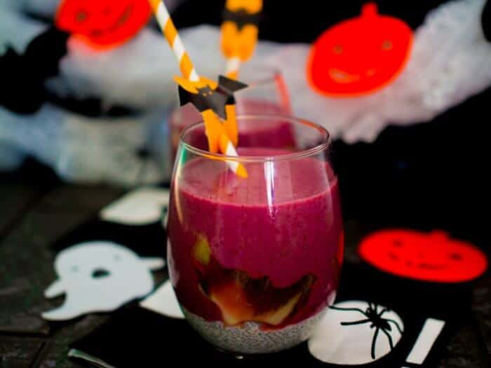 Berry colored smoothie in a glass decorated with bats