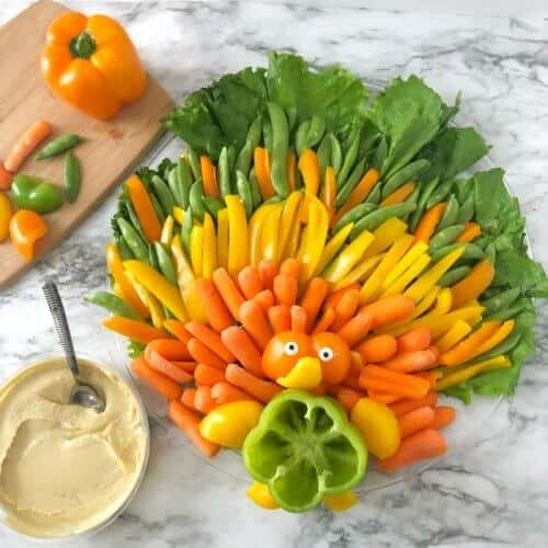 On the table is a vegetable platter shaped like a turkey with orange, yellow and green feathers made out of bell peppers, carrots, sugar snap peas and lettuce. In the center of the platter is a bell pepper cut to look like a turkey but arranged that you can fill the pepper with dip. A side of hummus with a spoon also rests on the table and a cutting board with several cut bell pepper pieces sits nearby.