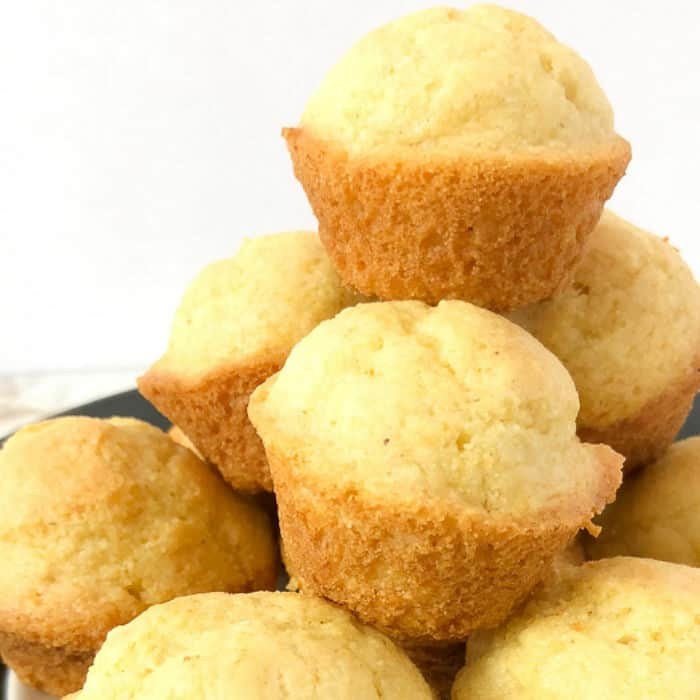 A close up view of a stack of sweet cornbread muffins piled high.