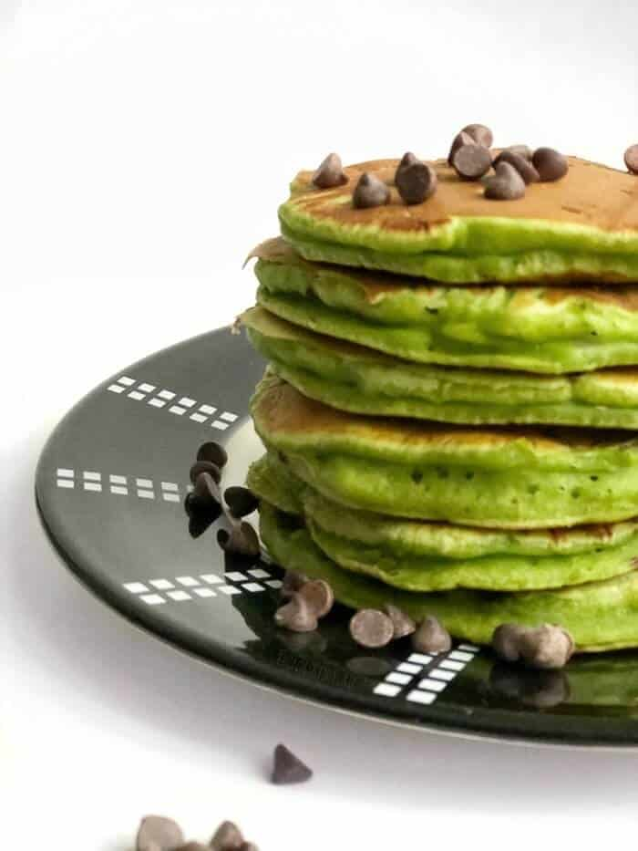 A stack of green spinach pancakes sits on a plate stacked high with a sprinkle of mint chocolate chips on top.