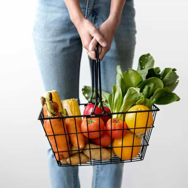A mom stands holding a grocery basket full of fruits and vegetables, we only see her legs and the basket.