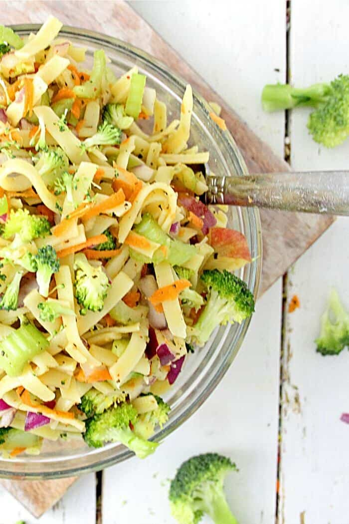 An overhead view of a bowl full of broccoli apple salad with pasta. The bowl sits on a cutting board coated in a lightly tangy apple cider vinegar and yogurt dressing.