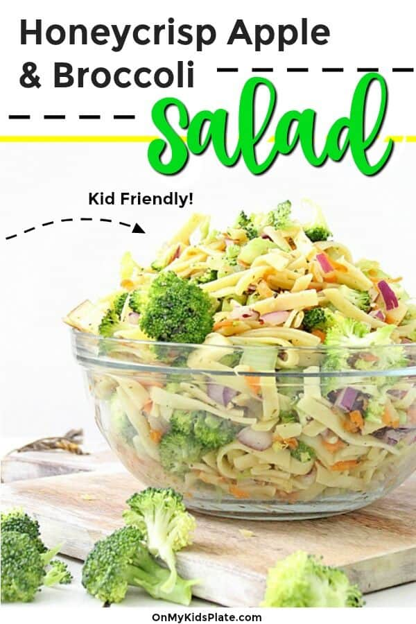 A bowl full of broccoli apple salad with pasta sits on a cutting board coated in a lightly tangy apple cider vinegar and yogurt dressing. On top of the image we see the headline Honeycrisp apple and broccoli salad, and an arrow points to the salad with the words kid friendly.