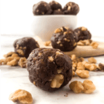 A bowl full of chocolate walnut energy bites sits on a counter with a few snack bites front and center surrounded by fresh walnuts.