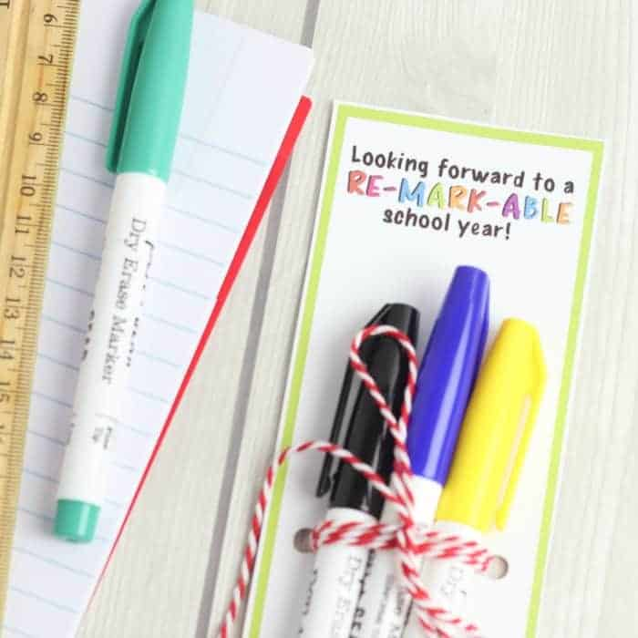 An easy diy first day of school gift for teachers is shown with a free printable tag. The tag reads looking forward to a remarkable school year and has three dry erase markers attached. The gift sits next to a ruler, and piece of paper.
