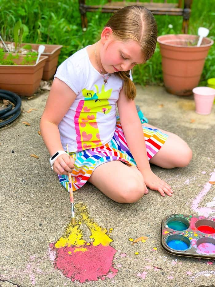 A child sits on the pavement with easy homemade sidewalk chalk paint and creates art on the pavement with a paintbrush.