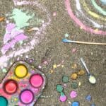 Colorful kid's chalk drawings, a paintbrush and spoon,  and homemade chalk paint in a muffin pan