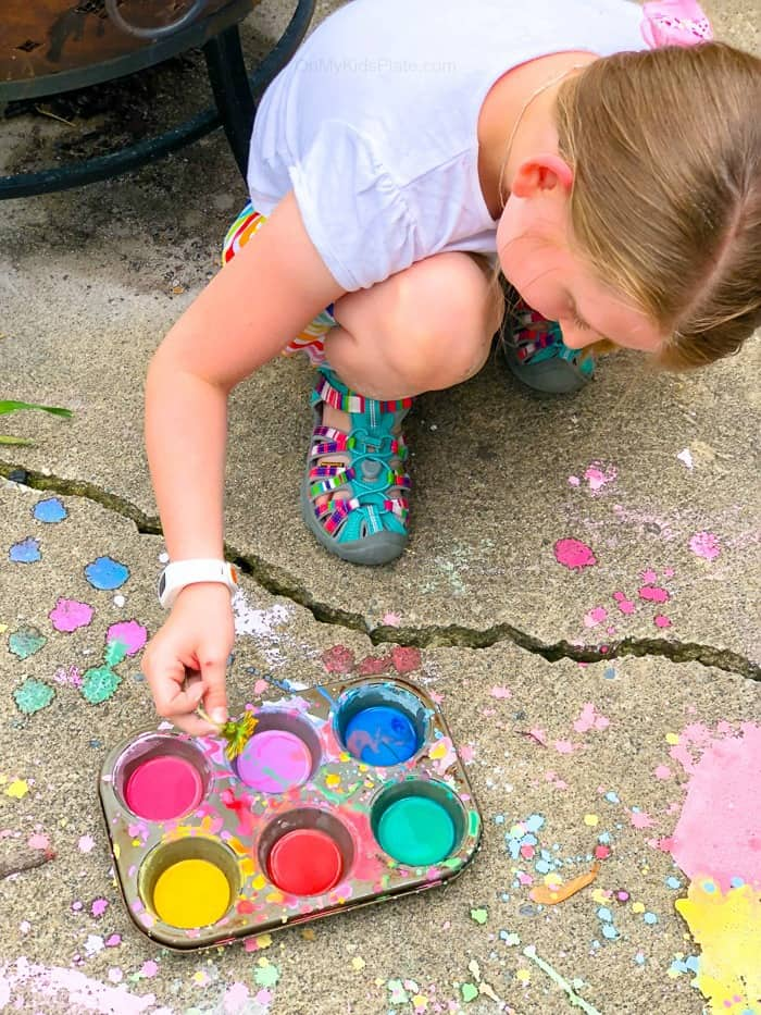 A child is painting on the sidewalk with a dandelion as a paintbrush next to a muffin tin full of colorful homemade sidewalk chalk paint and enjoying a fun summer activity.