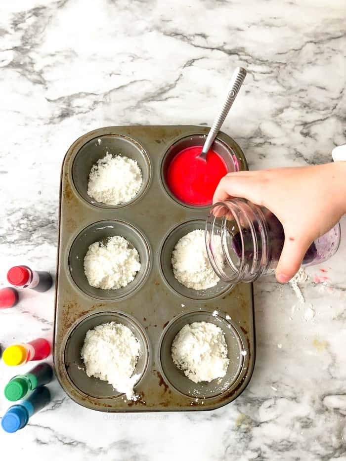 A child mixes colored water into cornstarch in a muffin tin to make DIY sidewalk chalk.