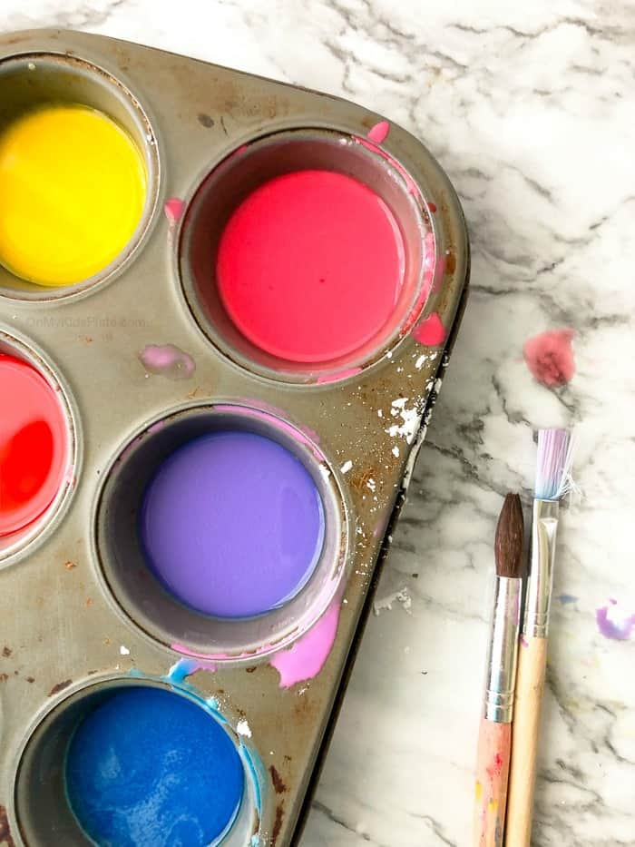 Colorful homemade diy sidewalk chalk paint sits in a muffin tin on a counter next to wide paintbrushes.