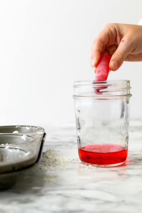 A child's hand drops food red food coloring into a small mason jar full of water to make homemade sidewalk chalk paint.