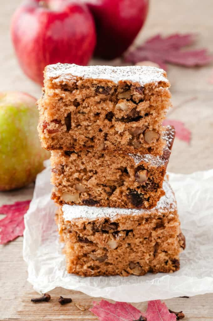 Three slices of cake stacked on top of each other on top of a piece of parchment paper with apples in the background