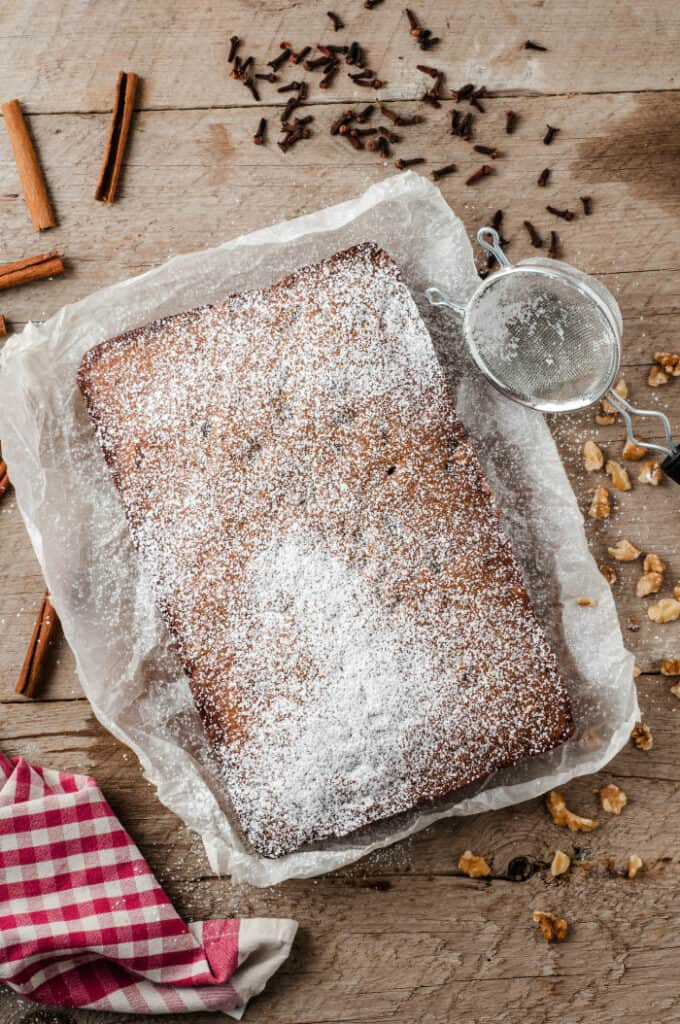 Full view of an apple walnut cake freshly decorated with a layer of powdered sugar on the entire top.