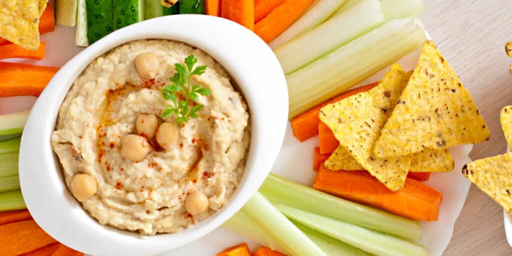 A bowl of hummus with celery, carrots, cucumber and tortilla chips to dip