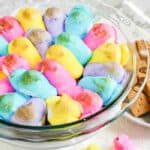 A baking dish full of gooey slightly golden brown chick shaped peeps in easter colors with chocolate underneath sits next to a plate full of graham crackers and cookies.