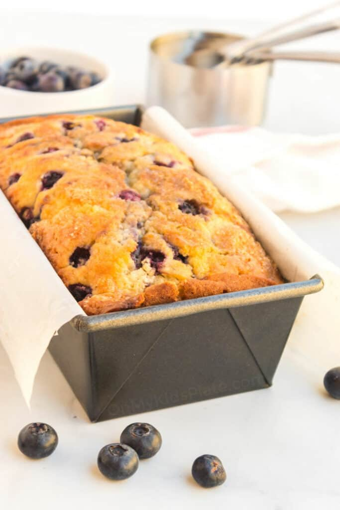 A lof of blueberry bread baked in the pan sits in front. Fresh blueberries and measuring cups fill the background.