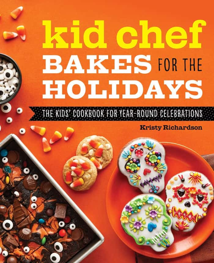 The cover of the cookbook Kid Chef Bakes For The Holidays. Day Of The Dead cookies, halloween brownies and candy corn cookies are all featured on the front.