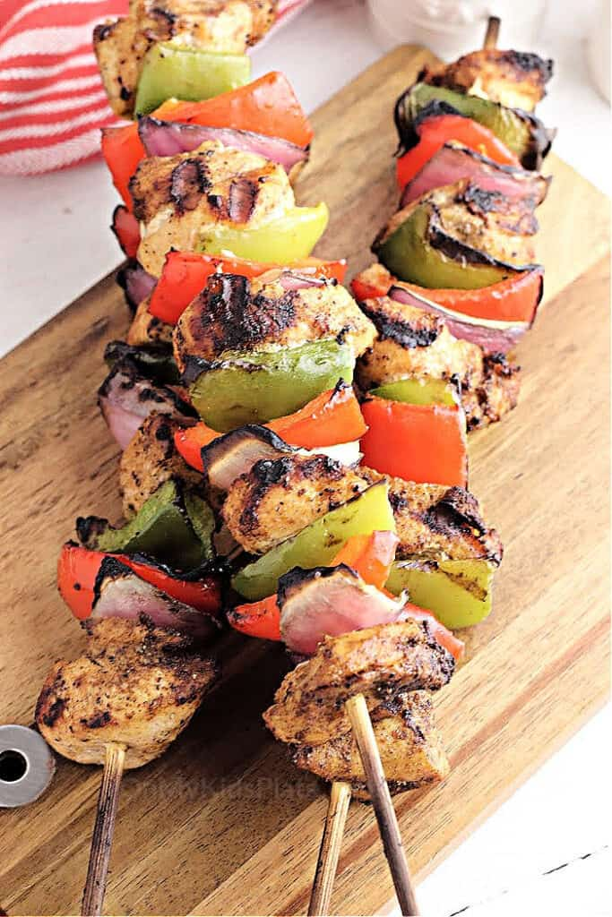 Marinated chicken kabobs on a wooden cutting board.