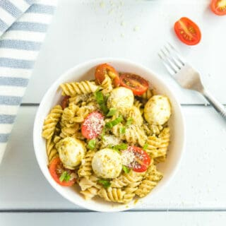 A bowl of cold pasta filling a bowl with pasta, basil pesto, cherry tomatoes and fresh mozzarella sits next to a napkin, a fork and a few scattered sliced cherry tomatoes.