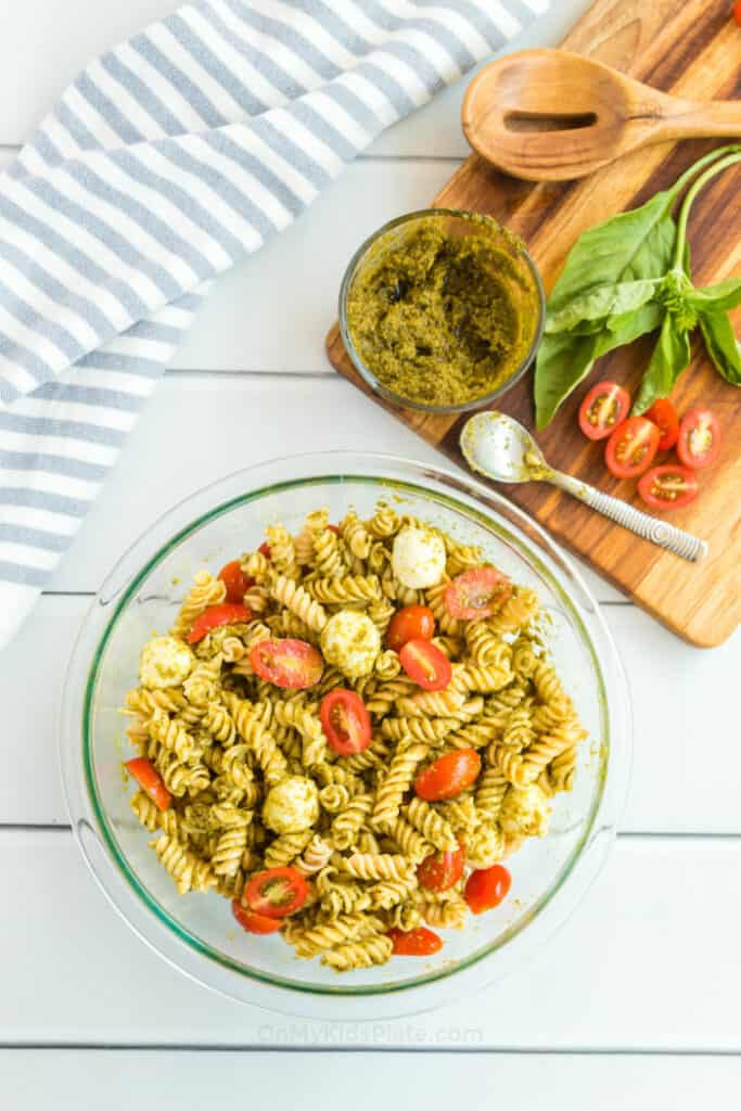 A large clear serving bowl of pesto pasta salad sits next to a kitchen towel and a cutting board full of ingredients.