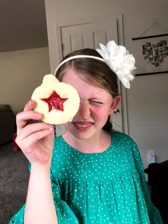 Young girl holds holiday cookie in front of her eye.